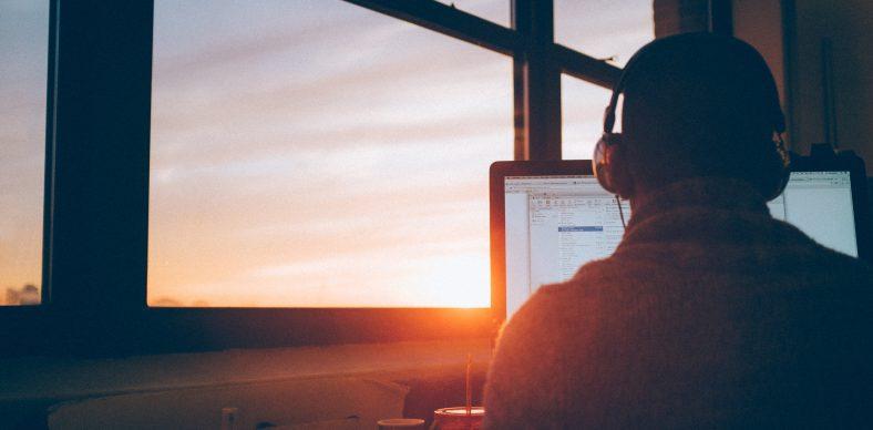Homme avec un casque devant un ordinateur