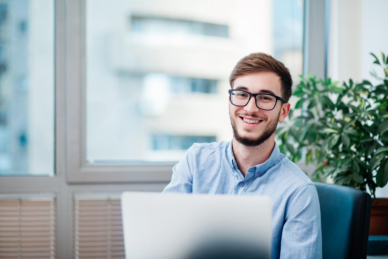 un jeune homme souriant sur ordinateur