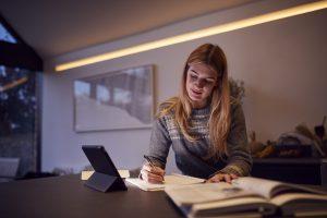 une femme entrain d'étudier avec sa tablette et cahier