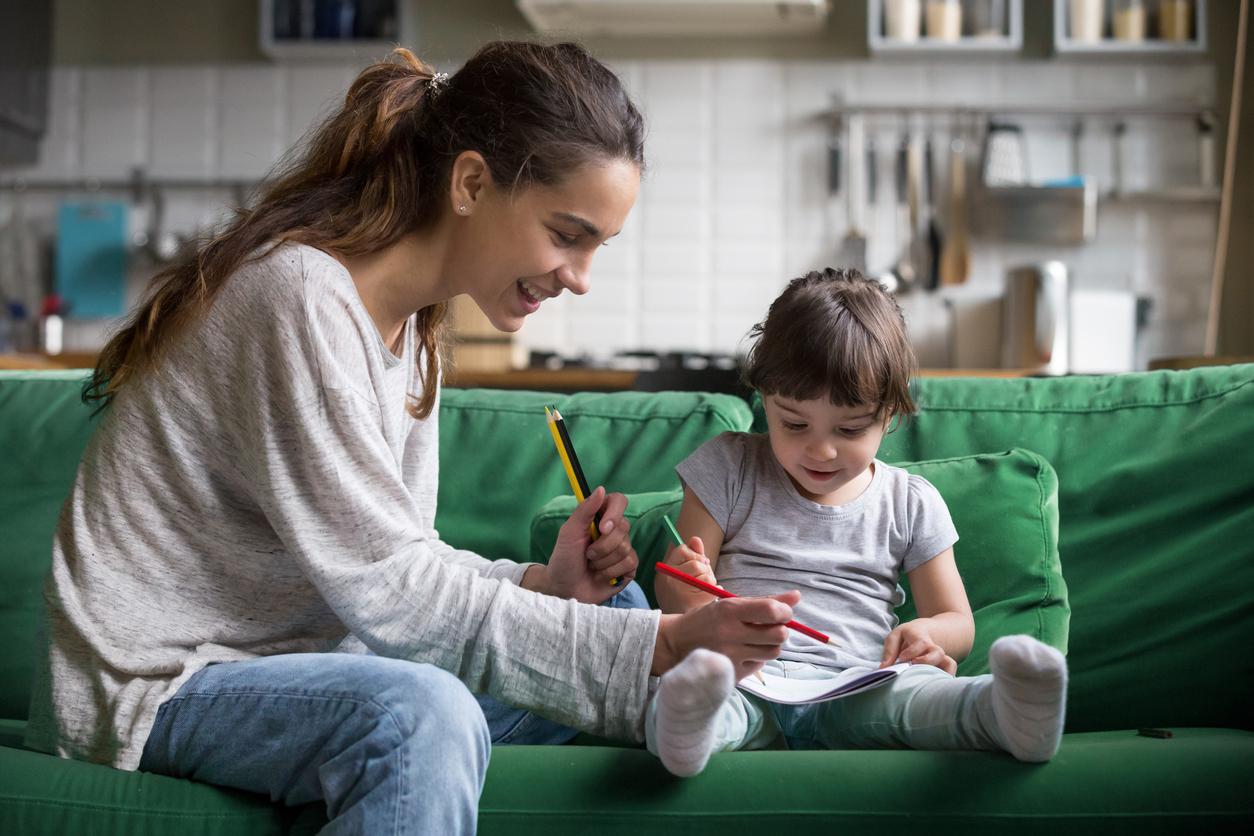 nounou dessine avec une enfant canapé