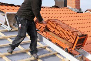 un professionnel disposant des tuiles sur un toit