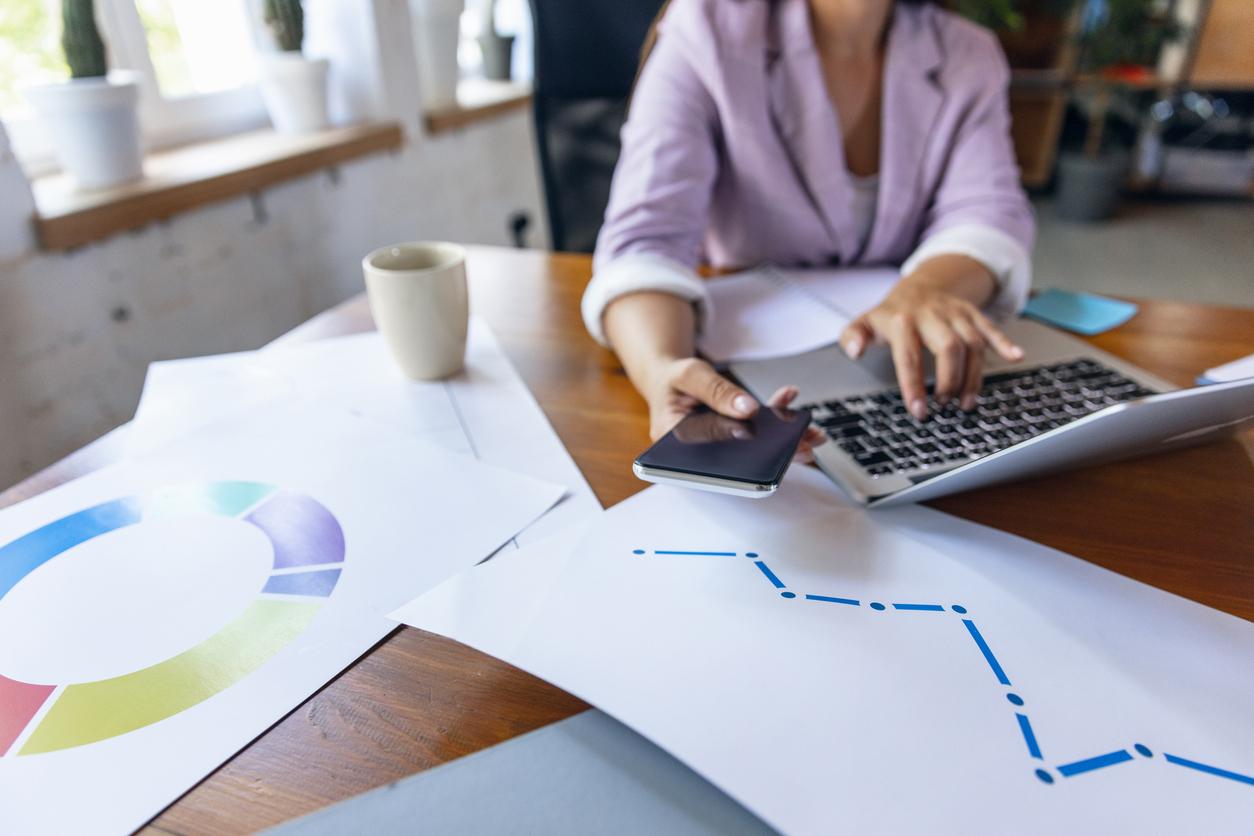 une femme sur son bureau avec documents financiers et son ordinateur