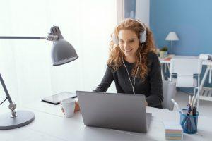 une femme souriante sur son ordinateur avec un casque