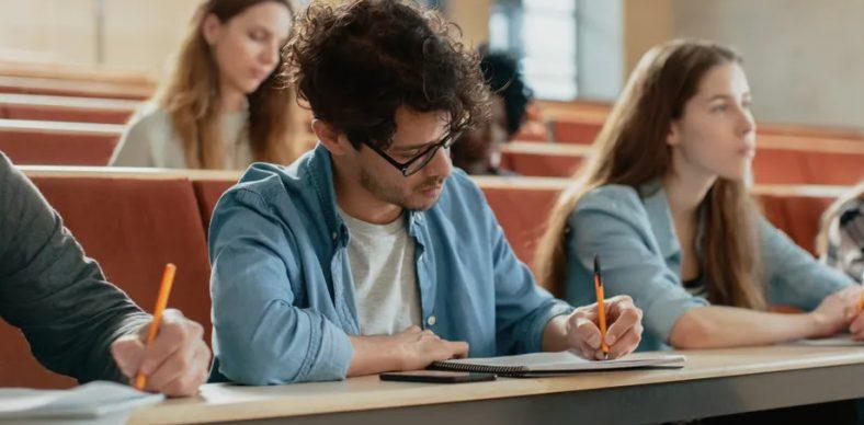 Etudiant qui écrit le cours en amphithéâtre